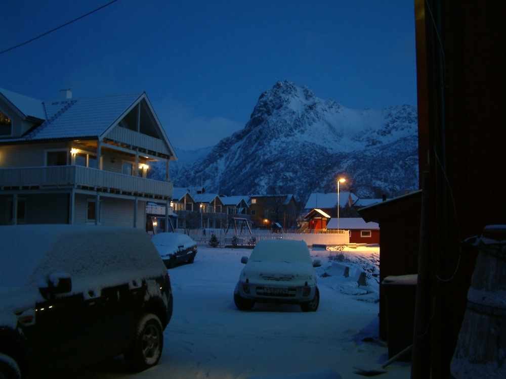 A snow covered street in the center of the Lofoten town Svolvær at dawn.