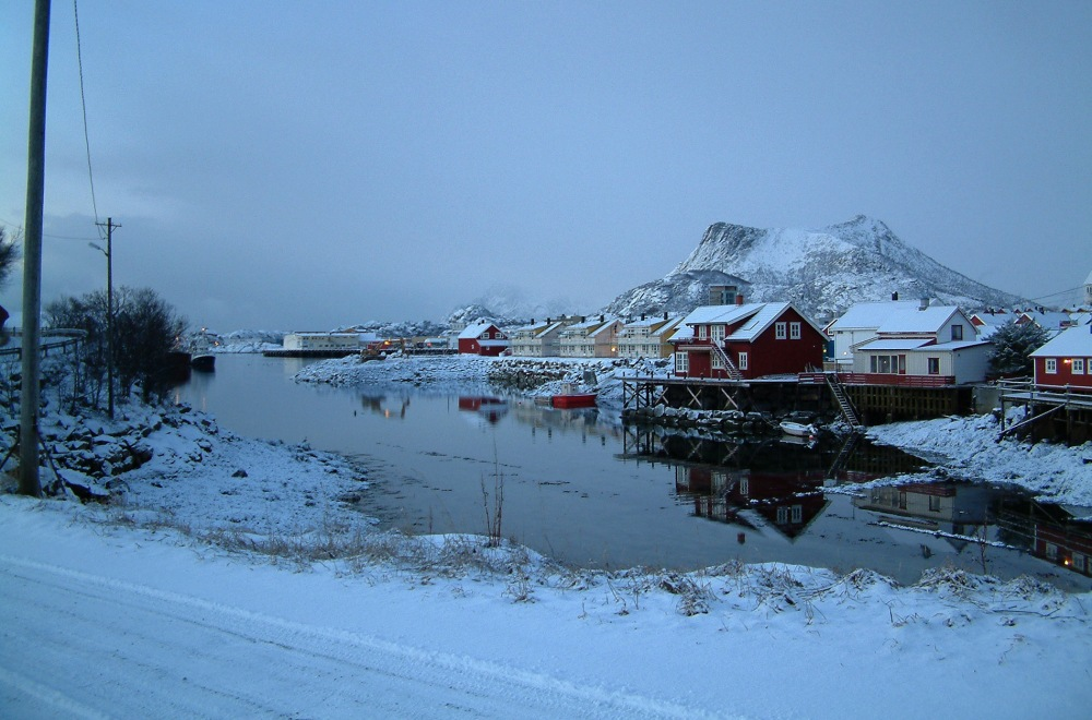 Colorful fishing houses line the fjord in the snow-covered town of Svolvær in Lofoten