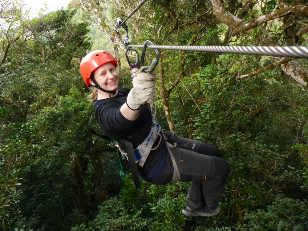 I'm sitting in a climbing harness, double clipped into the zip line cable, holding one hand out to avoid twisting.
