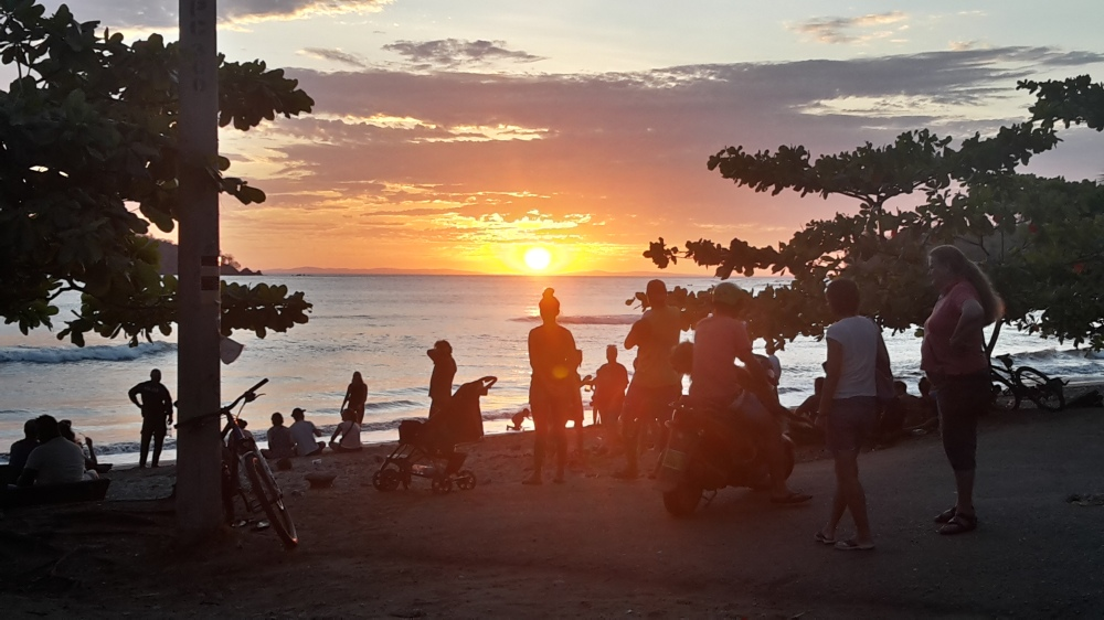 An orange sun disappears behind Coiba island as the locals gather at the Santa Catalina beach to watch.