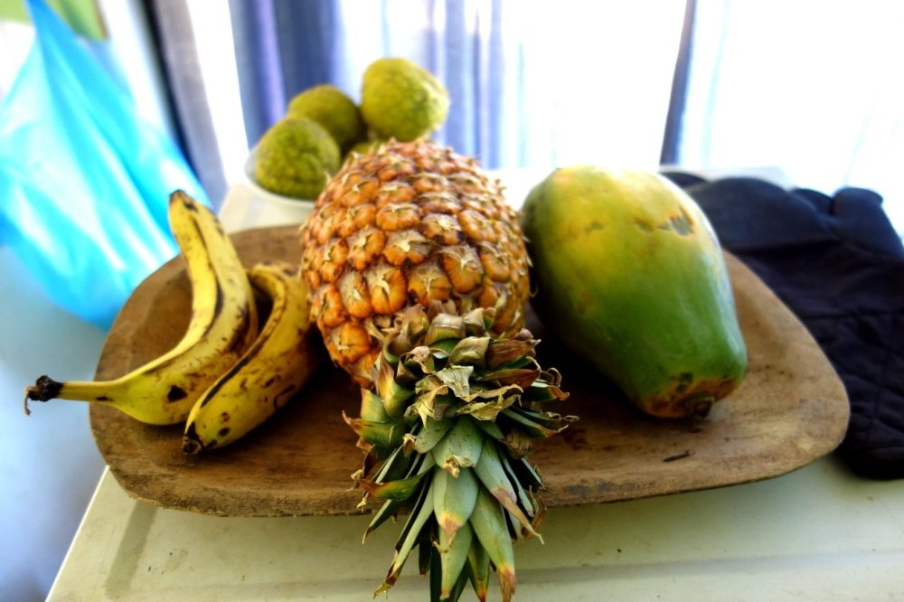 A wooden fruit plate loaded with bananas, a pineapple and a papaya.