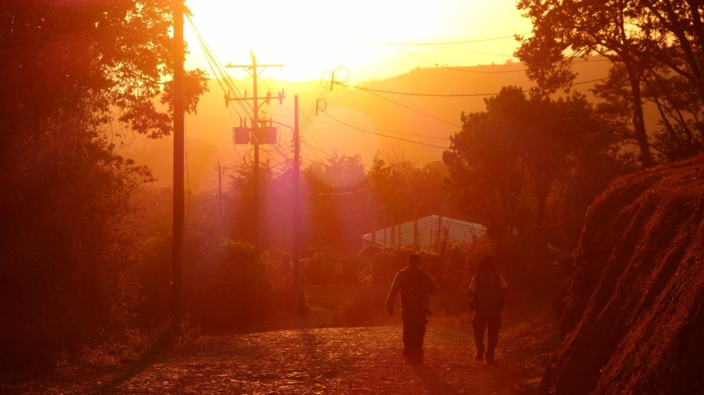 Two figures walking down a hill in Monteverde, bathed in the unreal red-orange glow of the setting sun